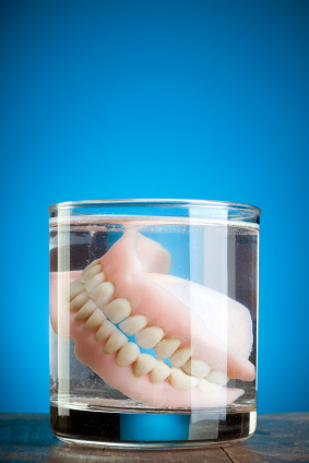 A pair of dentures floating inside a glass jar.